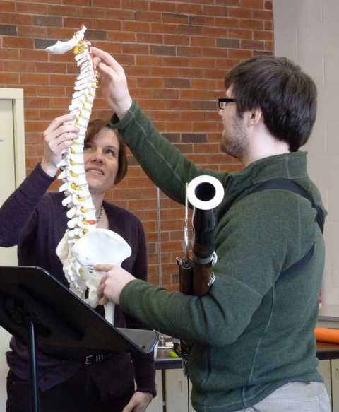 Body Mapping instructor Vanessa Mulvey and a student handle an anatomical model of the human spine.