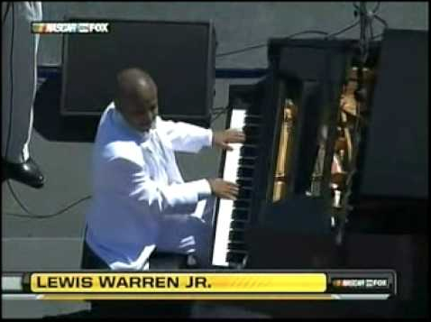Lewis Warren Jr. plays piano while wearing a white suit.