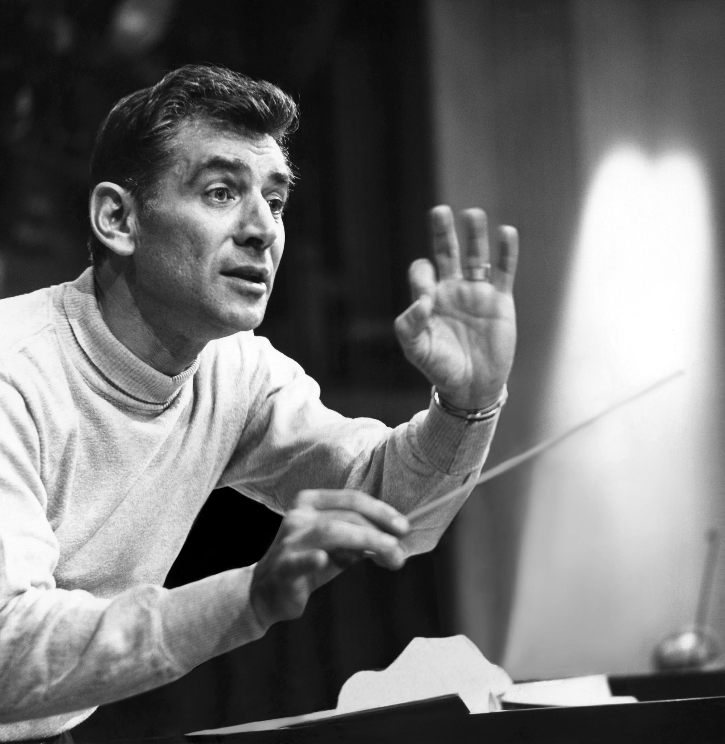 Leonard Bernstein conducting, holding a baton in his right hand.