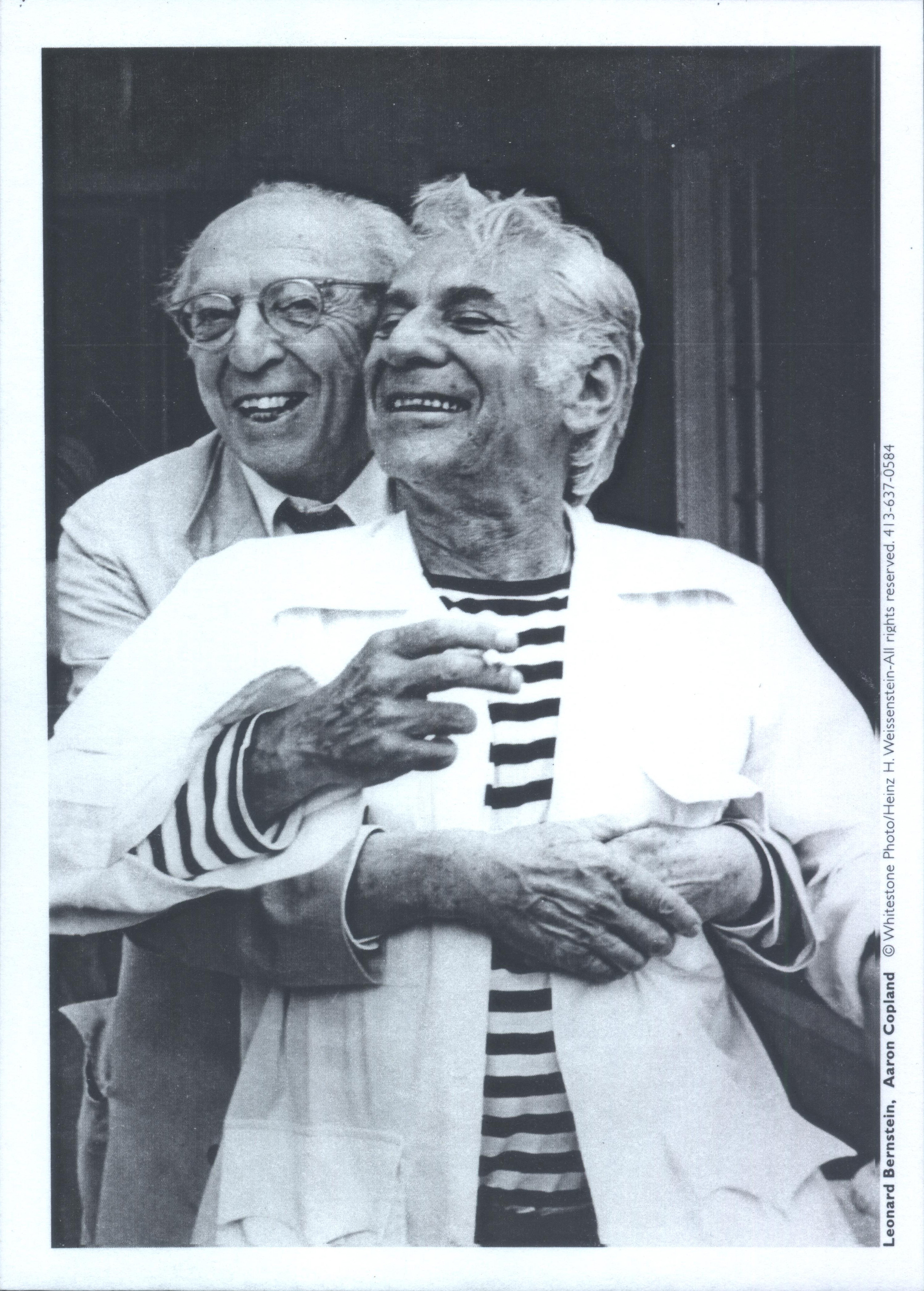 Aaron Copland hugs Leonard Bernstein. Both men are smiling.