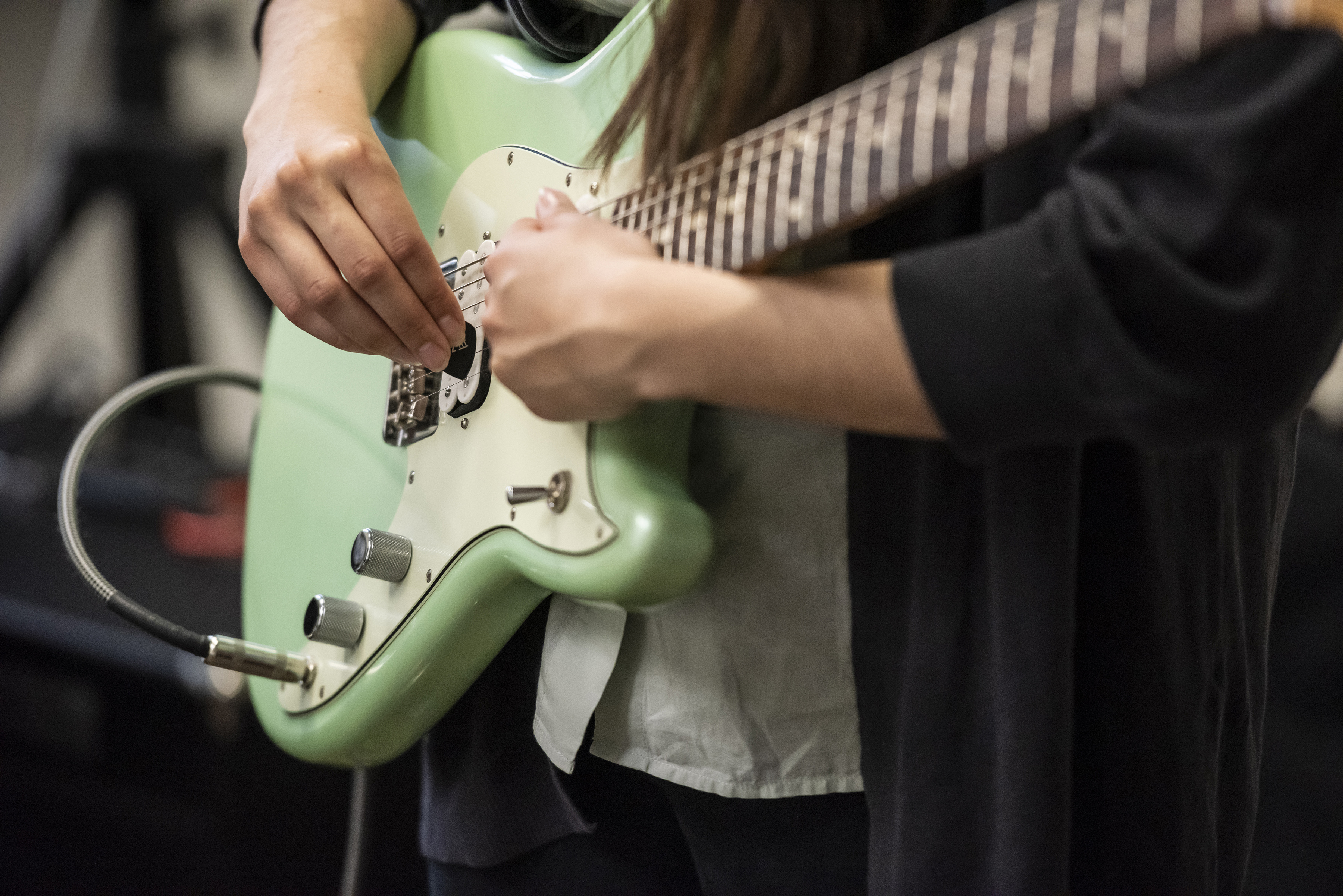 Close up of Magdalena's mint green electric guitar