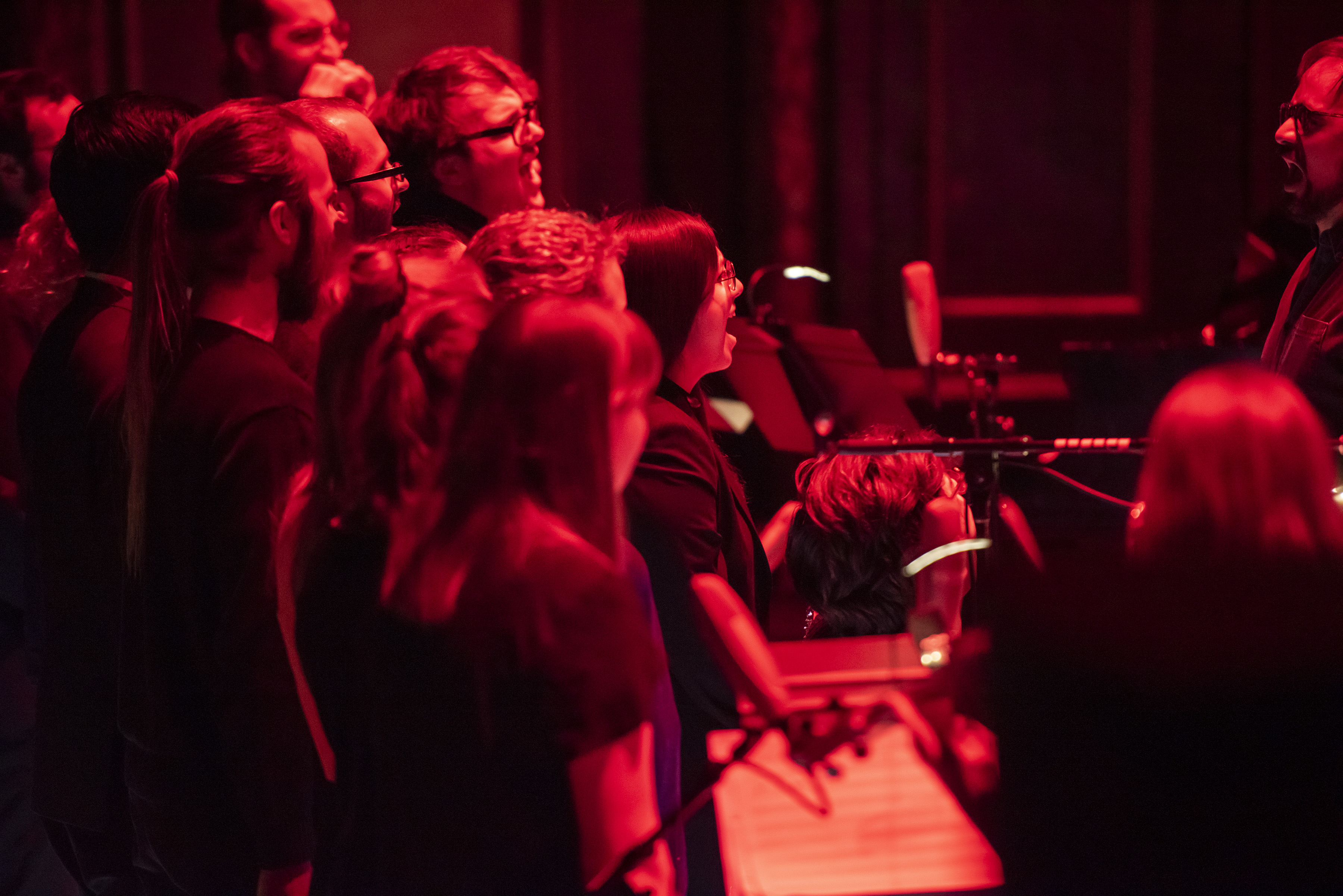 Red lights on students performing on Jordan Hall stage