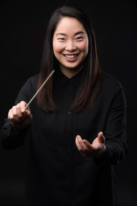 Holly Hyun Choe smiles and holds her conducting baton. She is wearing black and there is a black background.