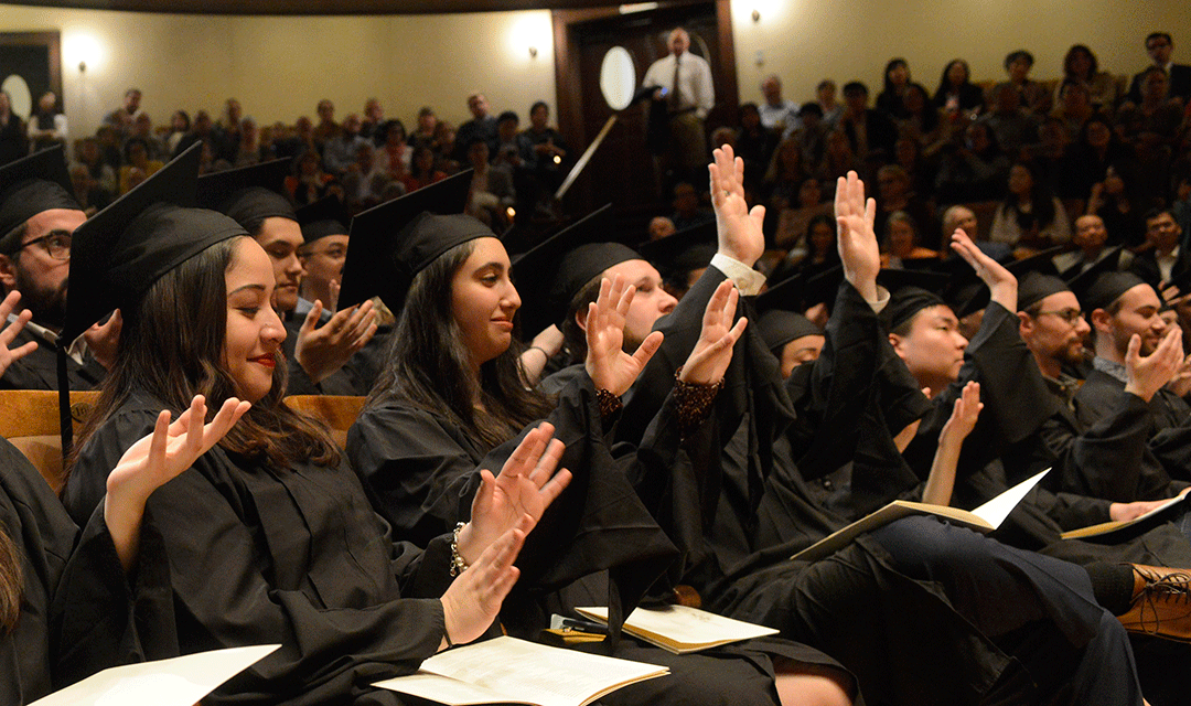 Graduates raise their hands in Jordan Hall