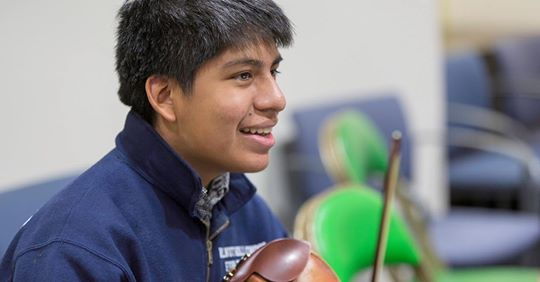 Noah Kelly, holding his violin and smiling.