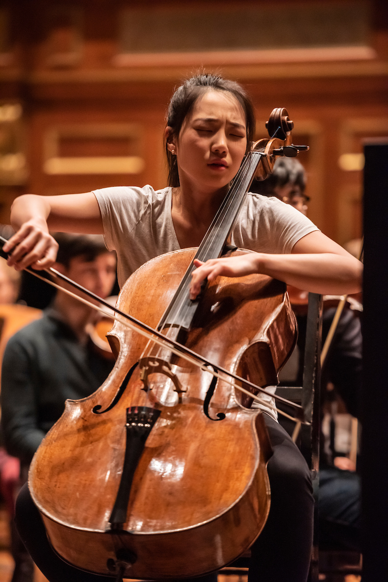 Claire Deokyong Kim plays the cello with an expression of emotion on her face.
