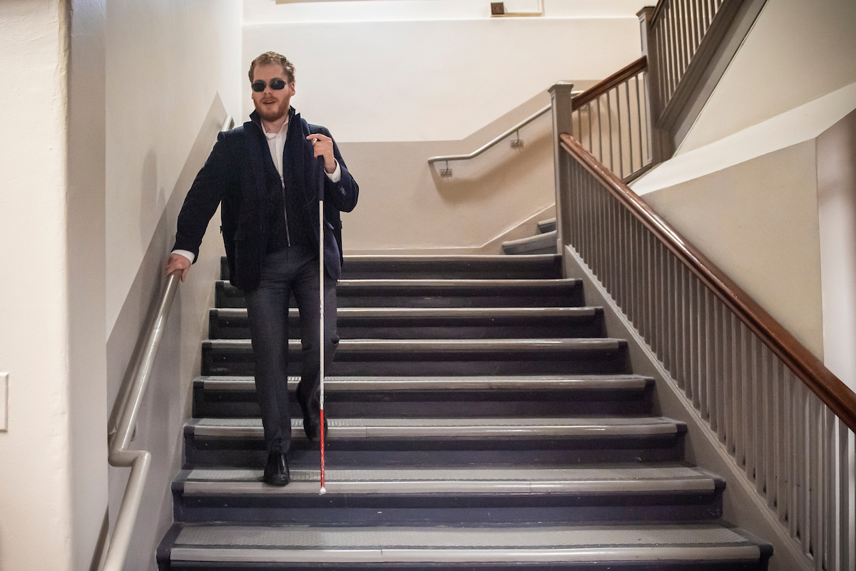 Student Matthew Shifrin descending stairs with his cane