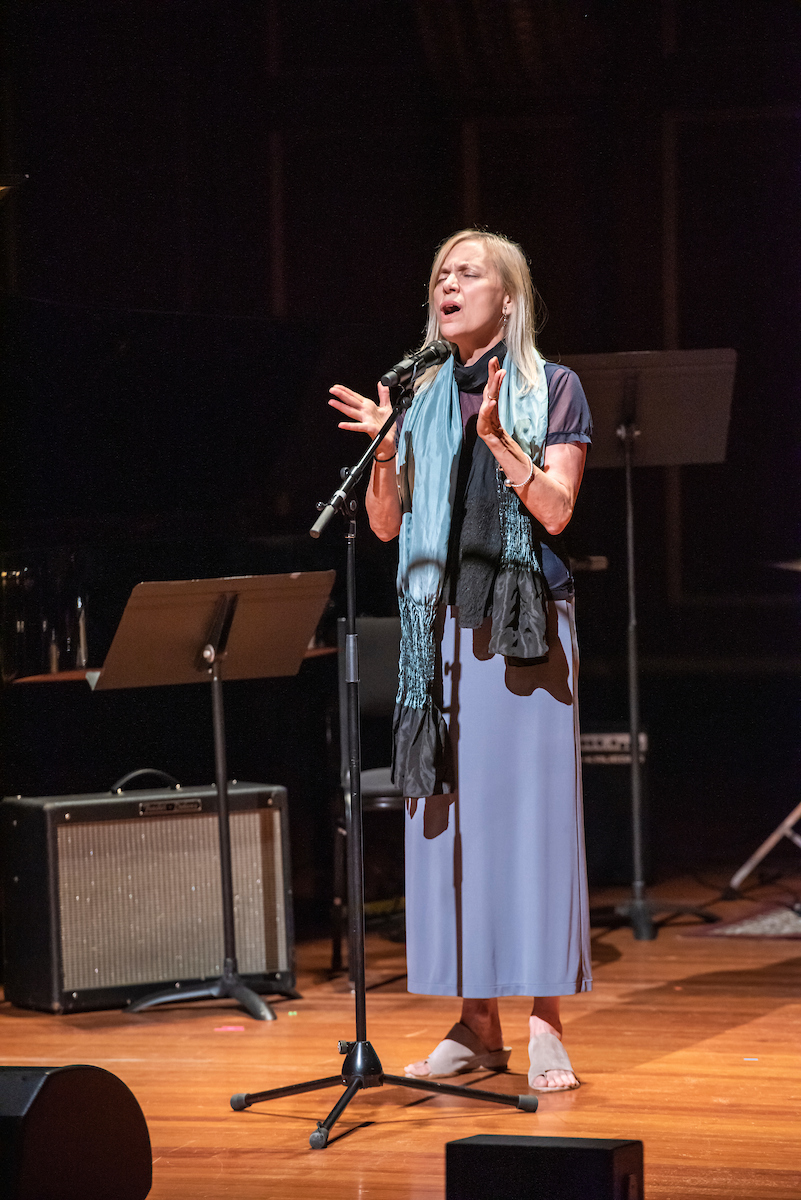 Dominique Eade closes her eyes and sings into a microphone in an unaccompanied solo performance in Jordan Hall.