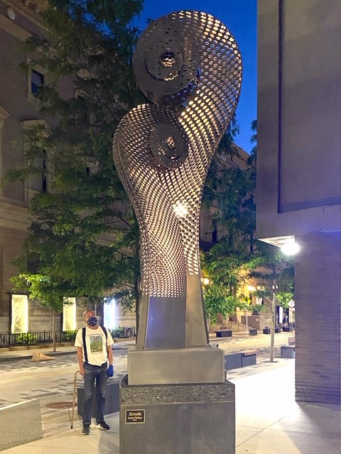 A large statue, approximately 20 feet high, with two scroll shapes like those at the end of a string instrument. The statue is metal, three-dimensional, and lit up from within. It stands at the corner of Gainsborough and St. Botolph streets. In this photo, a man stands at the foot of the statue looking up at it. He is wearing a face mask.