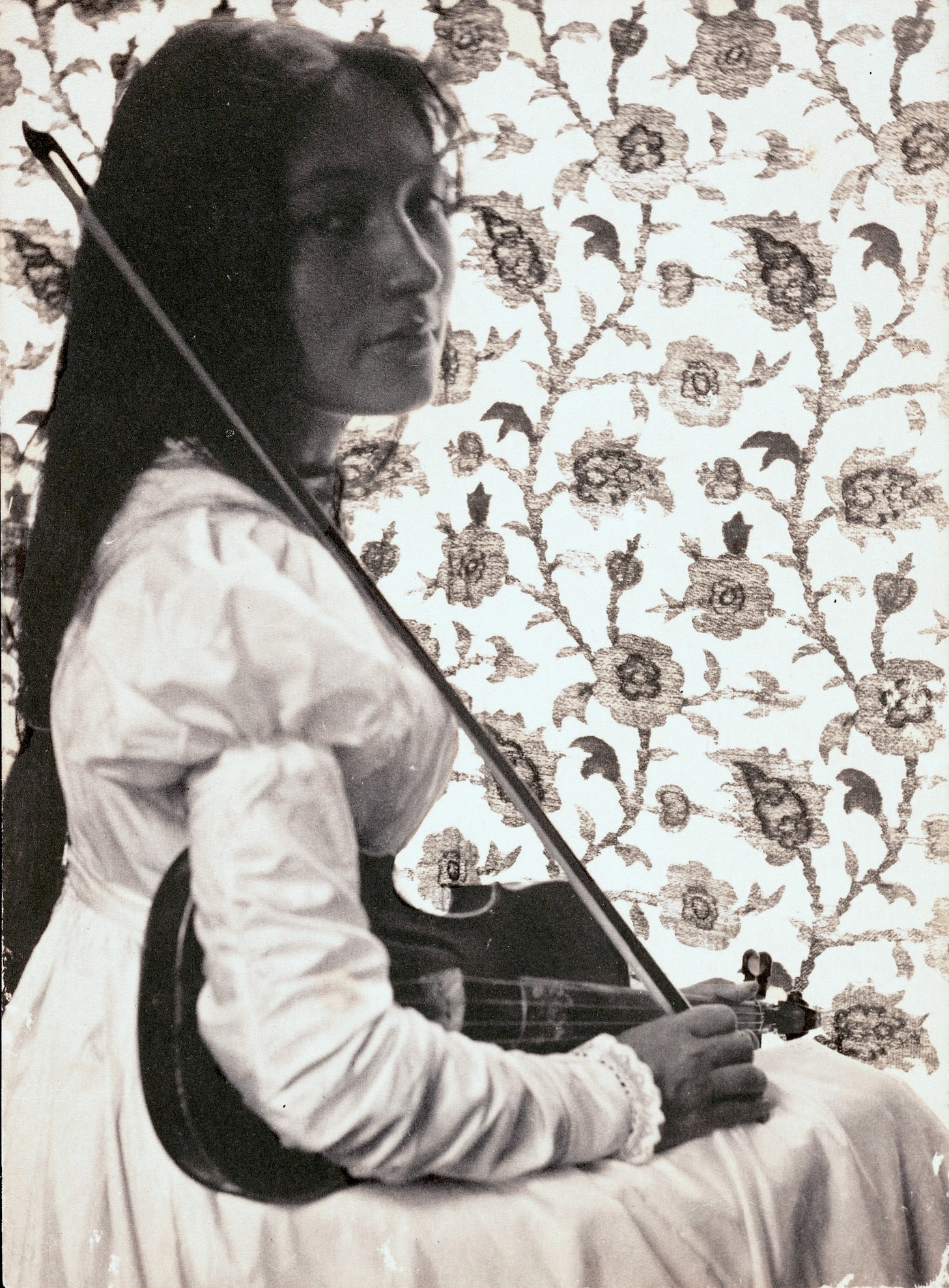 Portrait of Zitkala-Sa, wearing a white puff-sleeve dress, looking over her shoulder and holding her violin. The background is floral wallpaper.