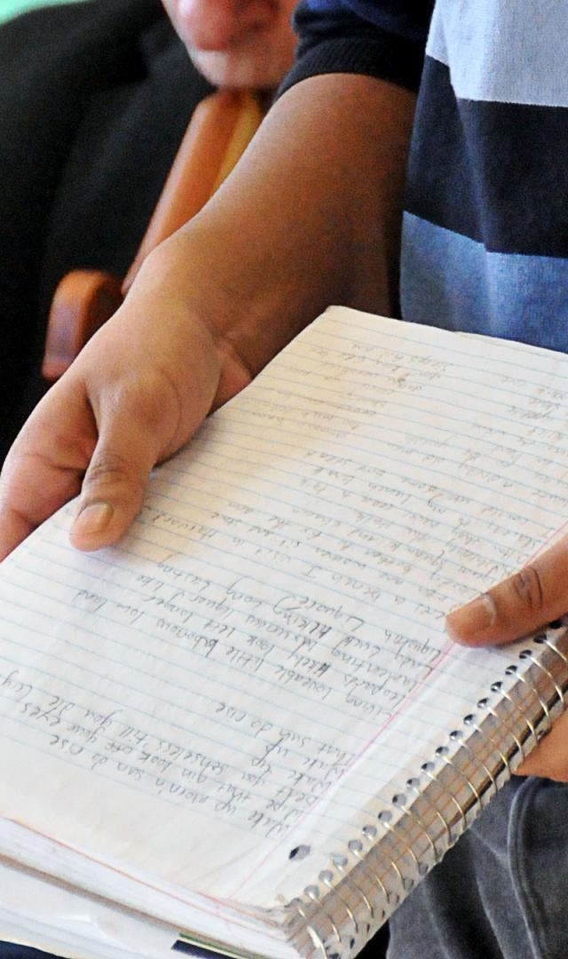 Hands holding a notebook of poems