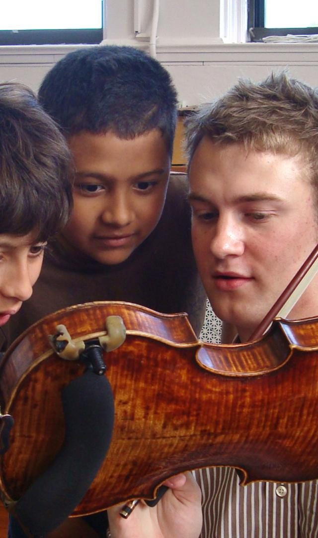 A violinist show his instrument to two interested kids