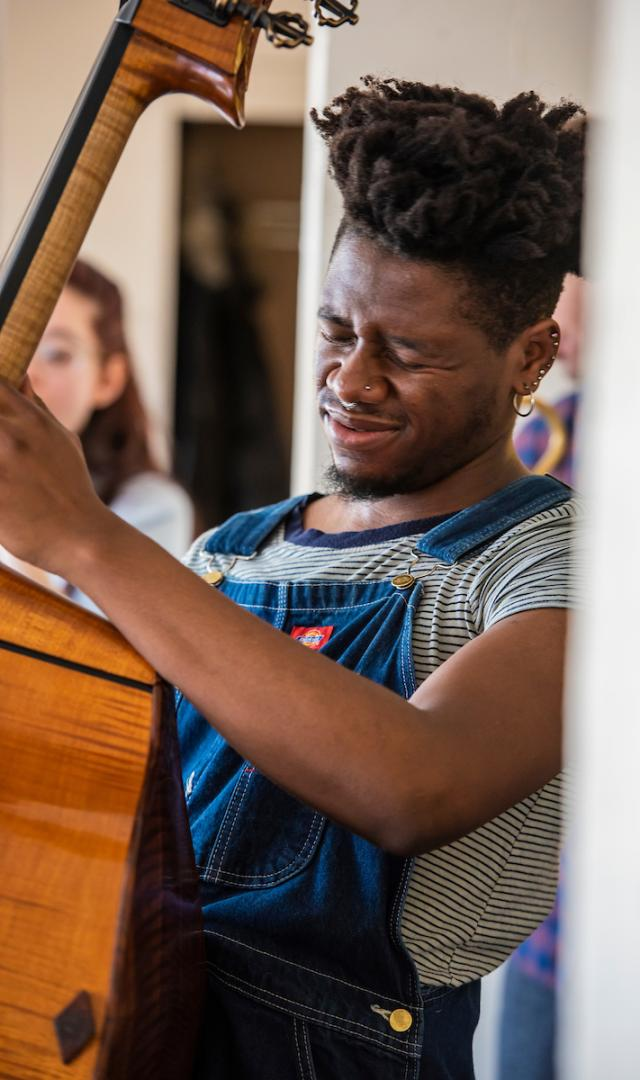 Kebra Charles makes an expressive face while playing double bass