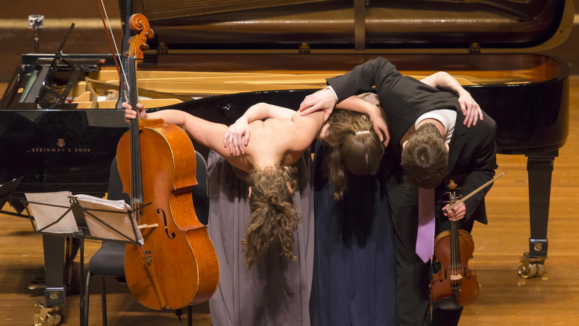 A piano trio bows at the end of a concert