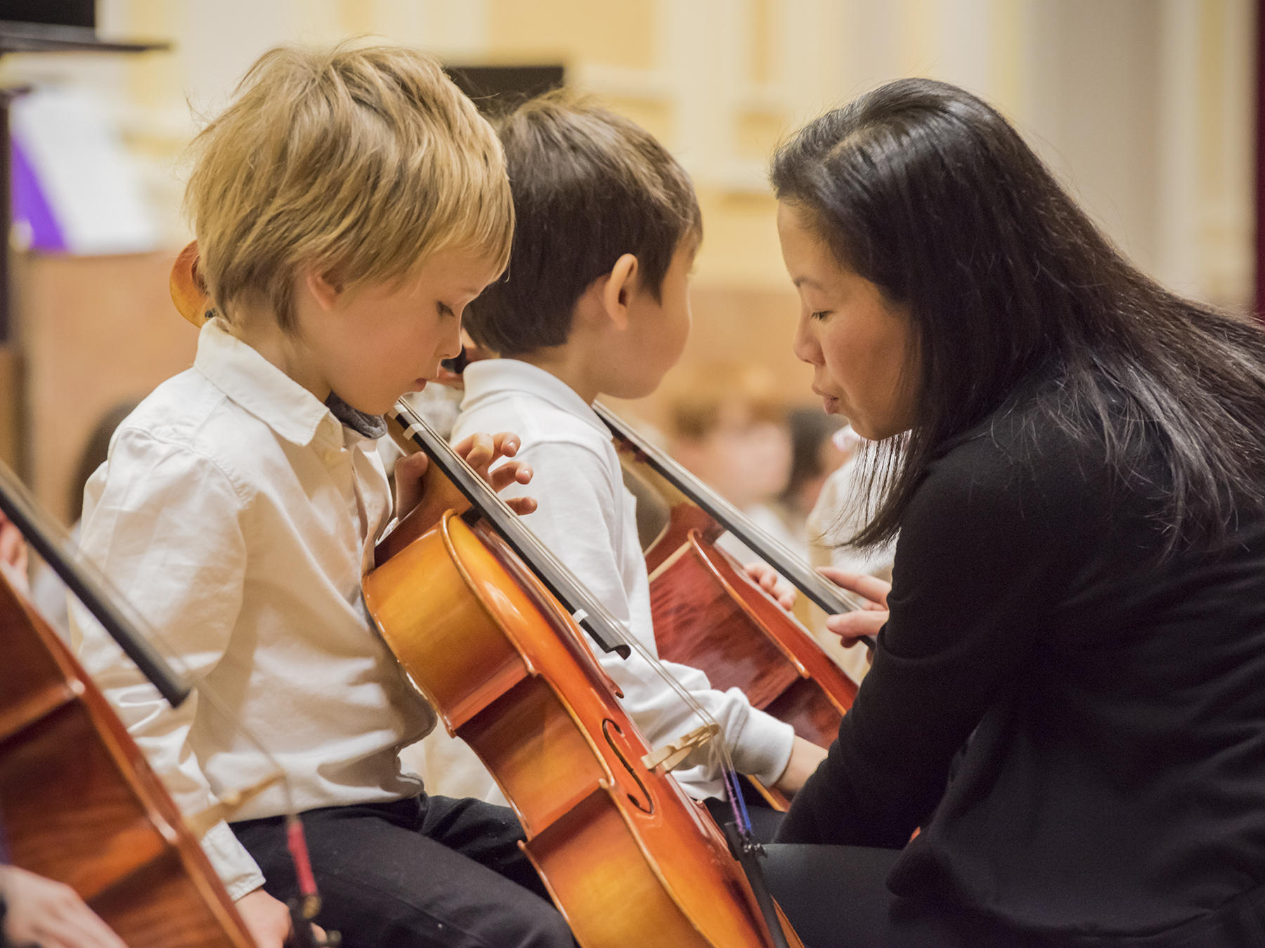 A Prep teacher helps a Suzuki cellist tune