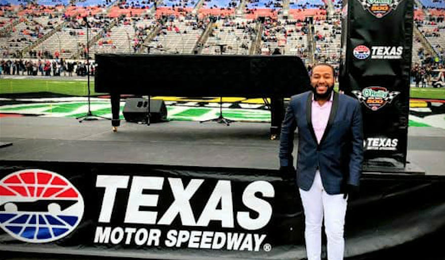"Lewis Warren Jr. poses with piano in front of a banner that reads ""Texas Motor Speedway."""