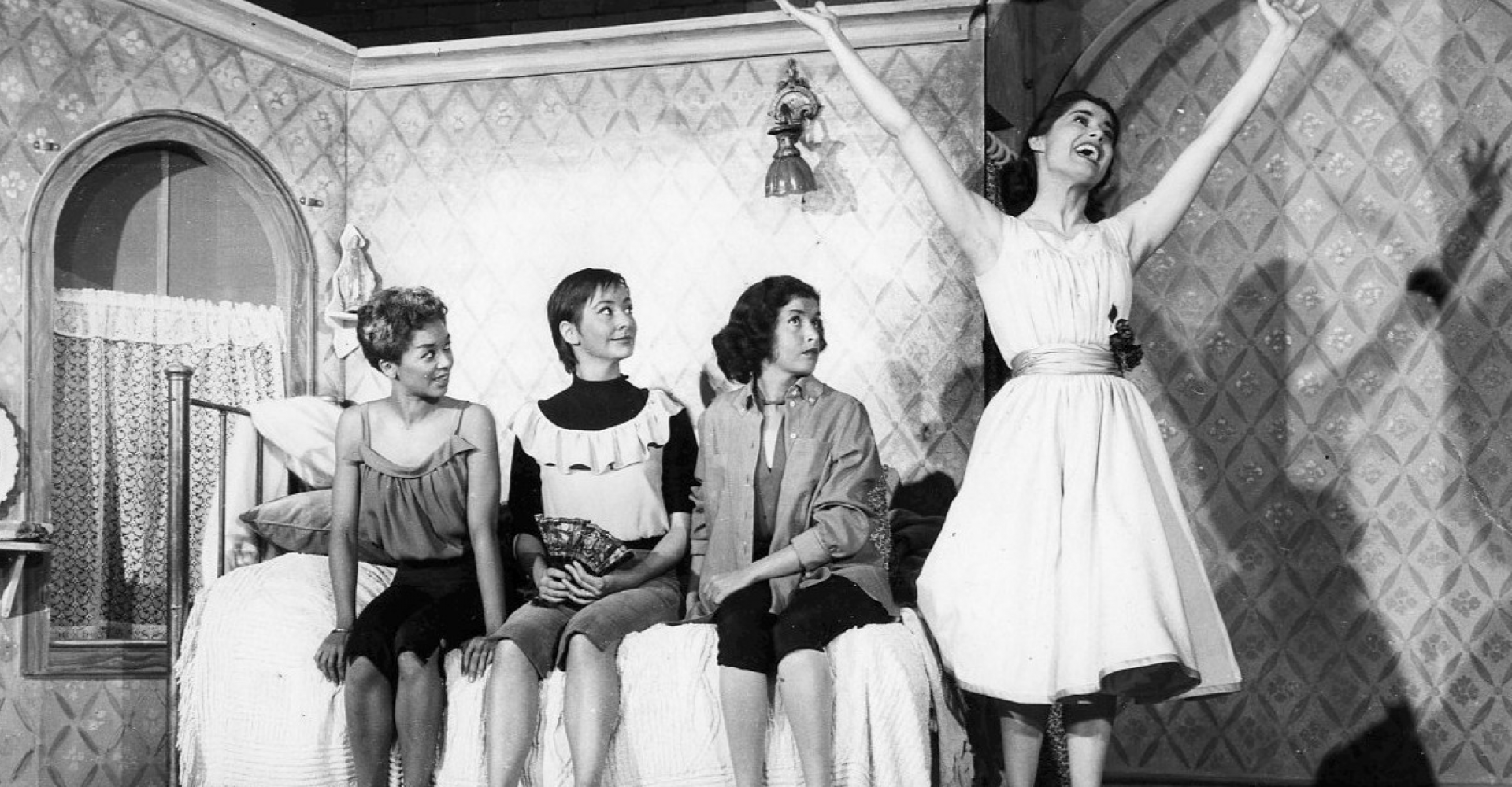 A scene from West Side Story, Maria smiles and opens her arms wide, while three women sit on a bed and look at her.