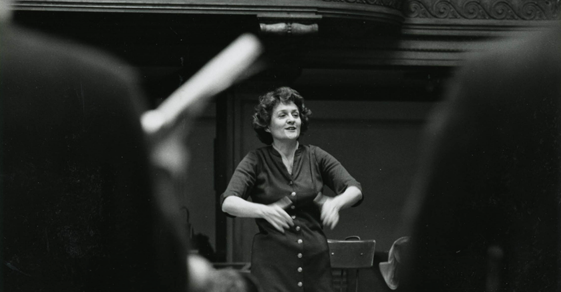 Lorna Cooke deVaron conducts, in a photo taken from the perspective of the chorus.