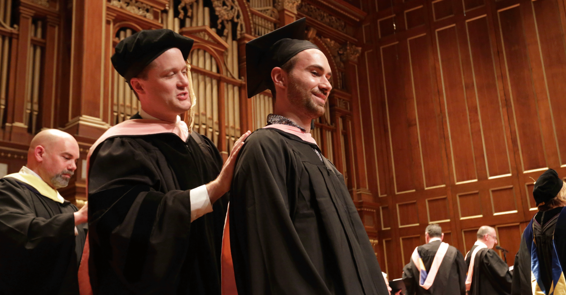 Alex Powell awards a master's hood to a graduate on the Jordan Hall stage