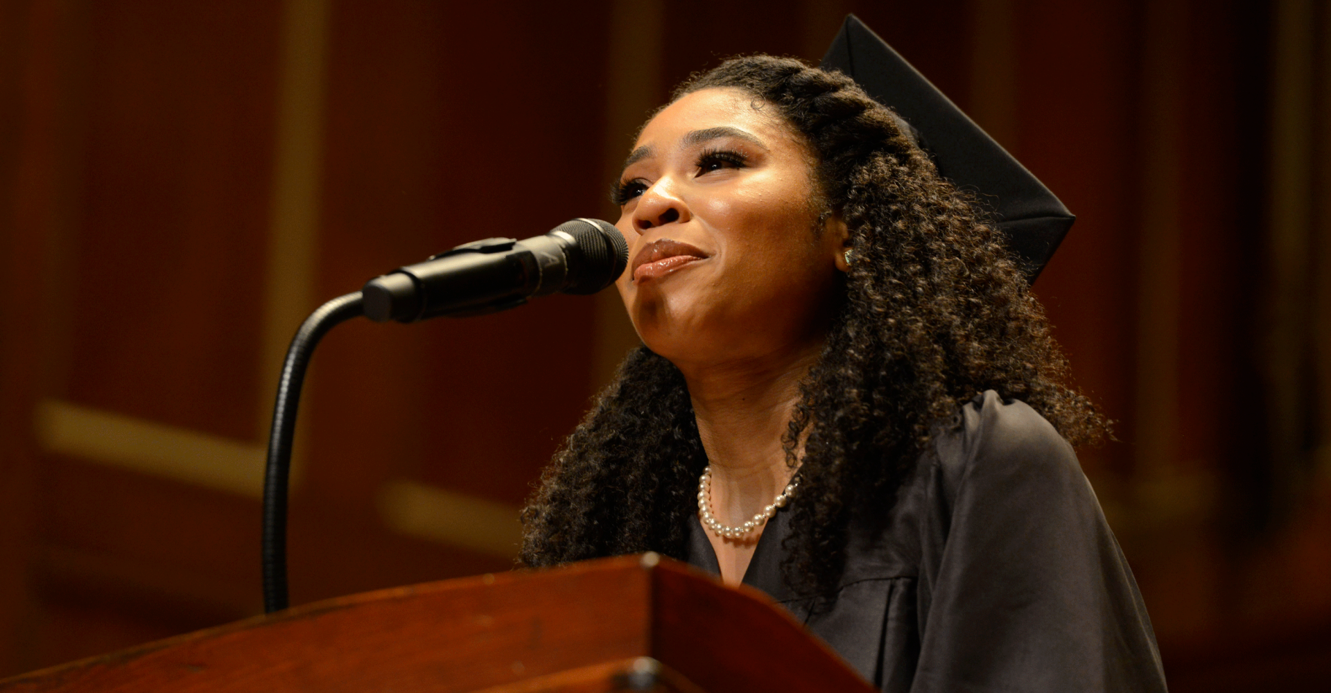 Darynn Dean stands at a podium wearing a graduation cap and gown. She smiles and looks into the distance while speaking into a microphone.