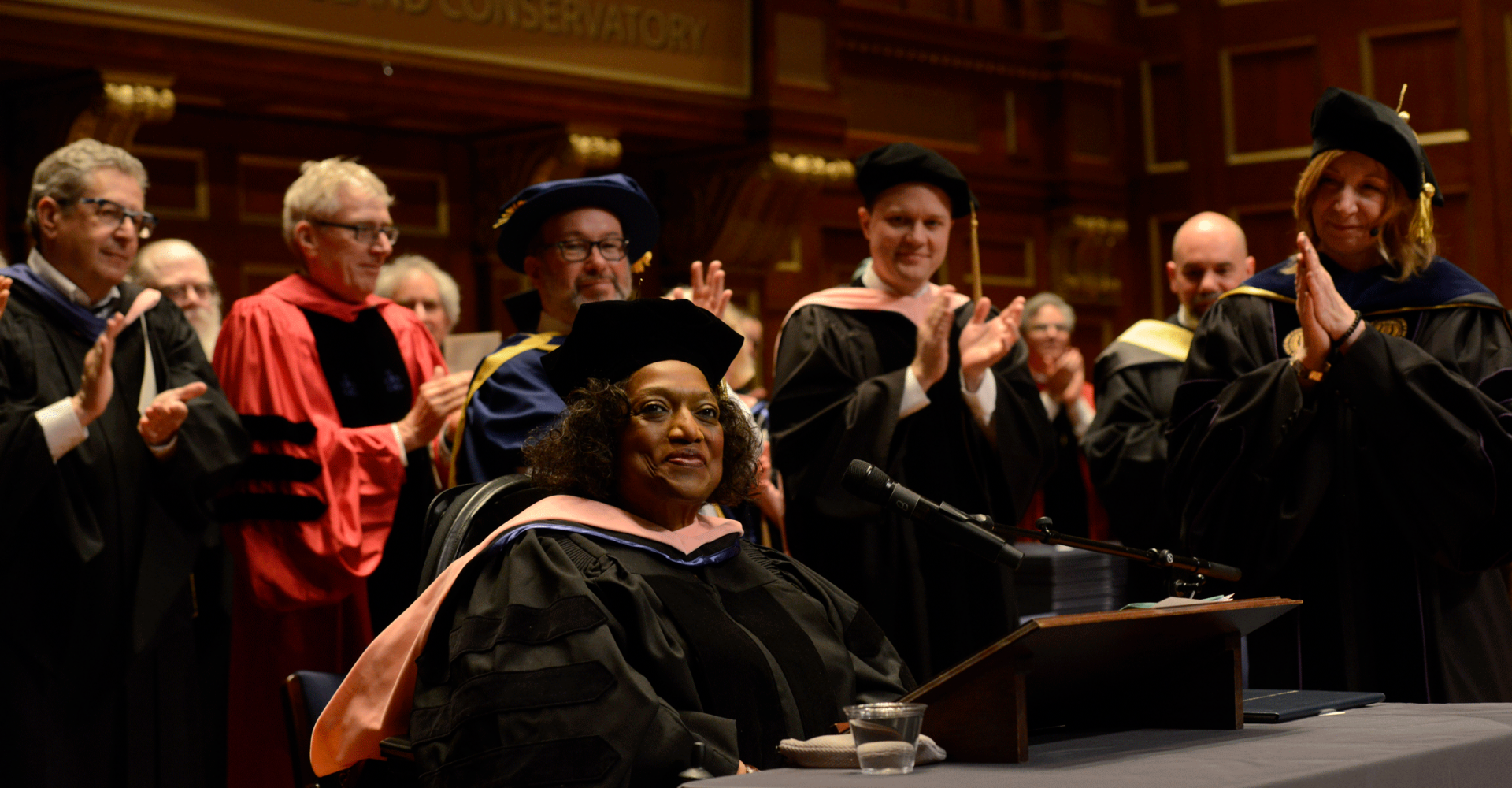 Jessye Norman smiles on the Jordan Hall stage while faculty applaud after she gave a keynote address