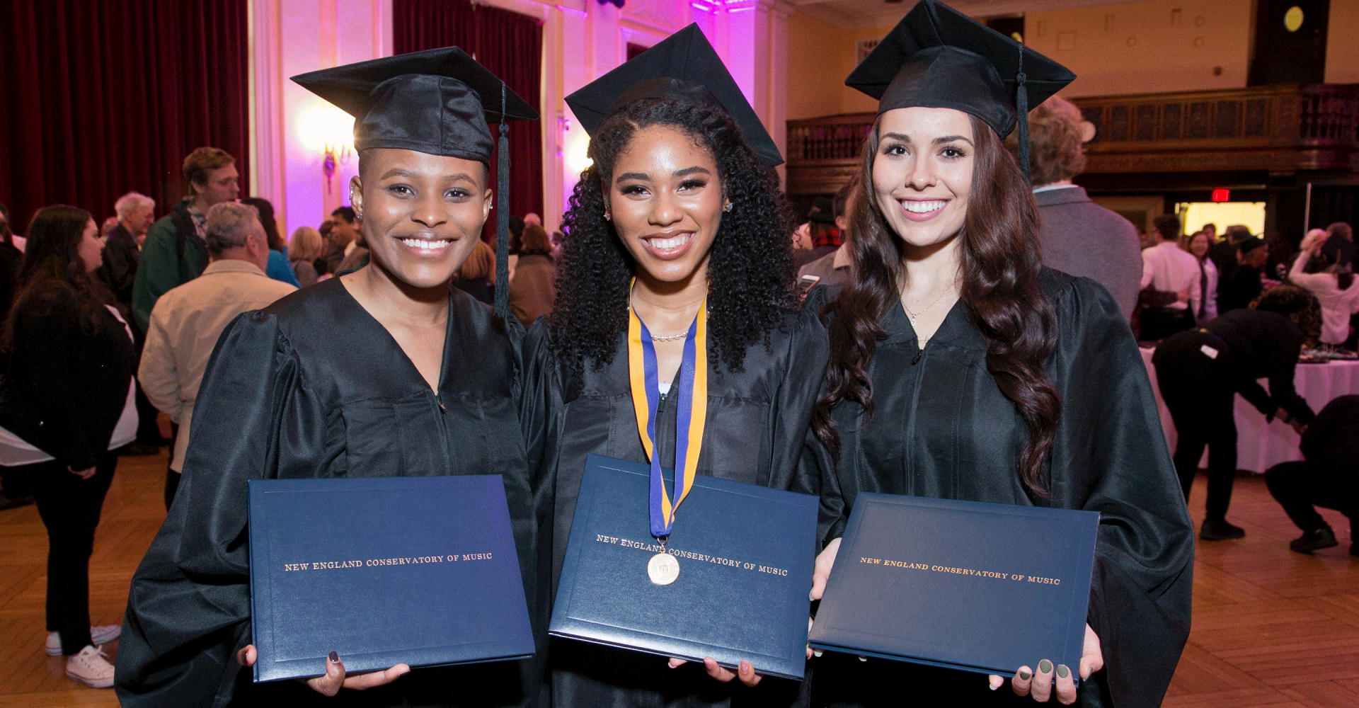 Three graduates smile and hold up their diplomas, wearing caps and gowns
