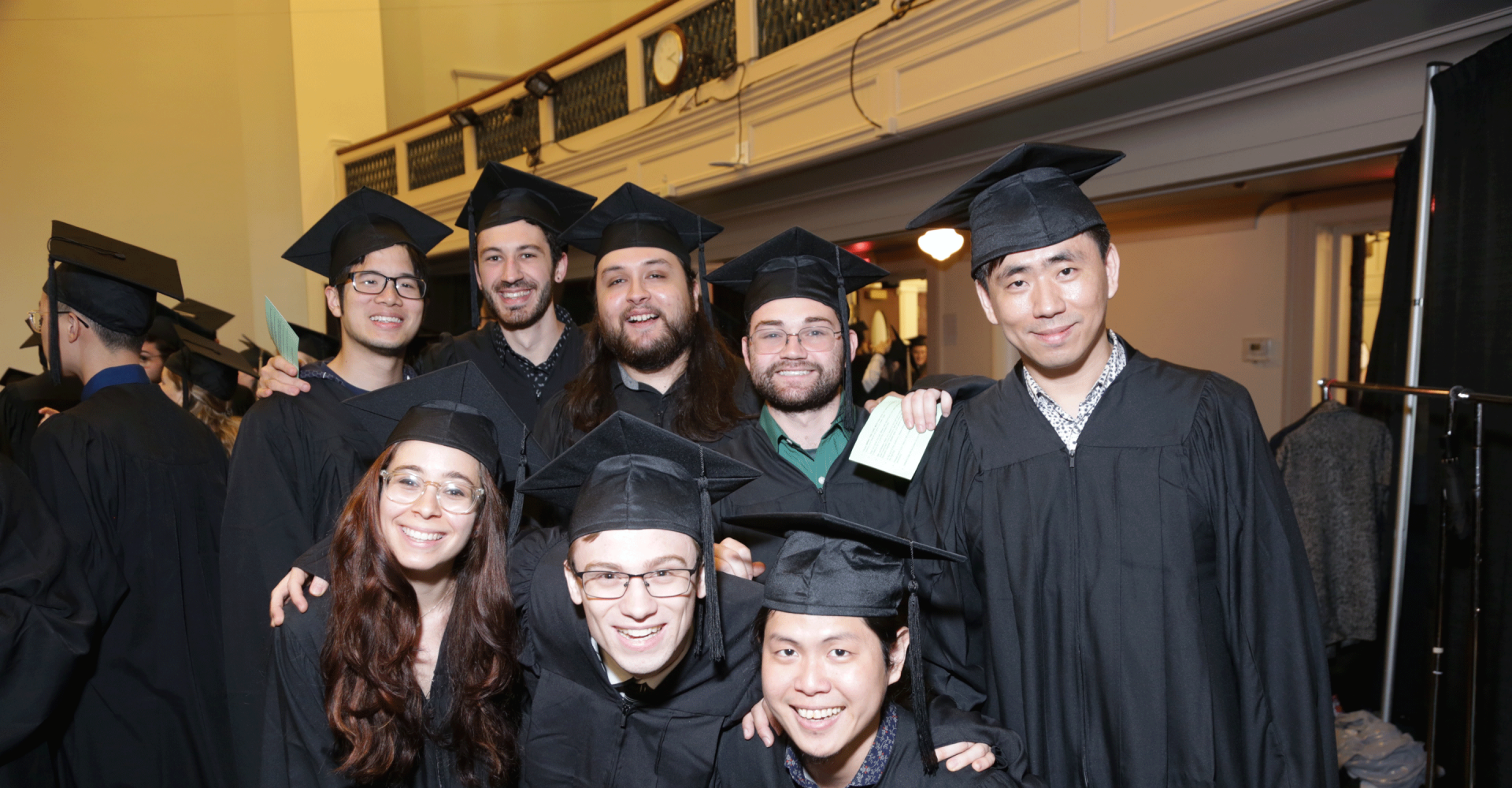 Eight smiling graduates wearing caps and gowns