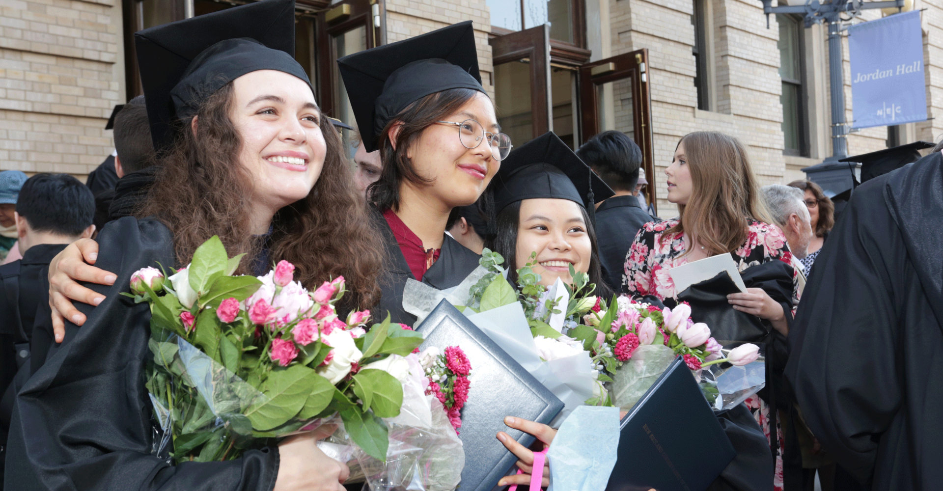 Students smile while wearing caps and gowns while holding bouquets in front of Jordan Hall
