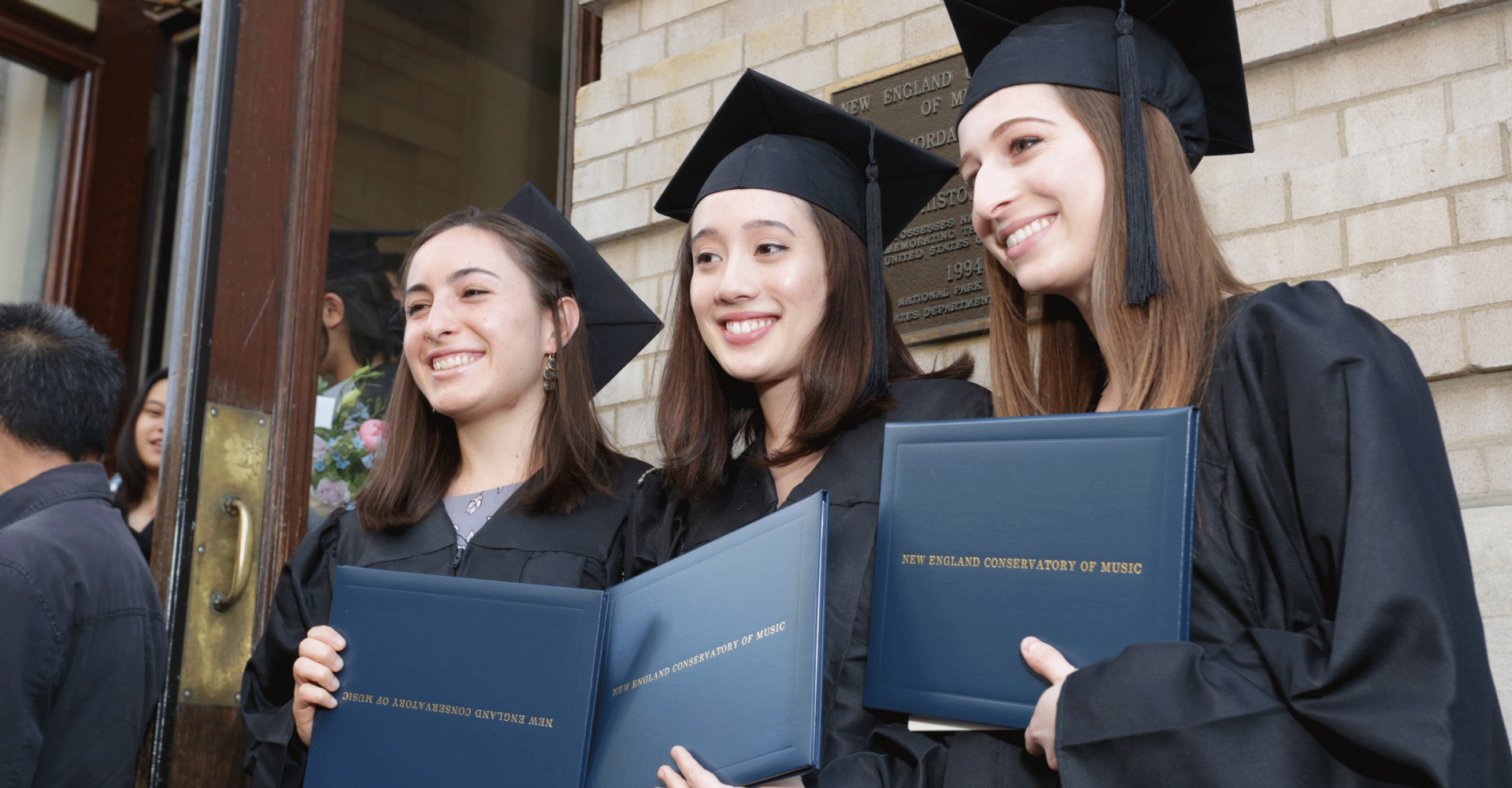 Three graduates smile and hold diplomas, standing on the steps of Jordan Hall