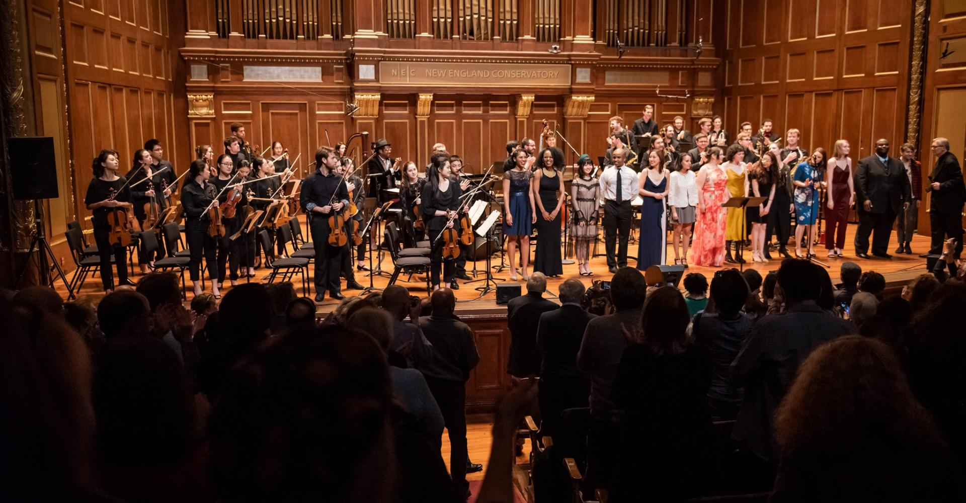 Performers take a bow in Jordan Hall while the audience stands and applauds