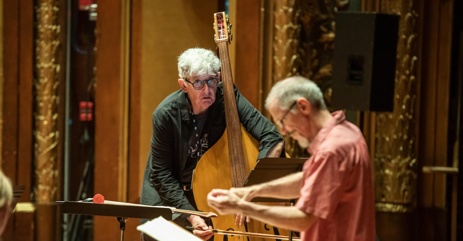 Mark Dresser plays bass and looks closely at conductor Steve Drury.