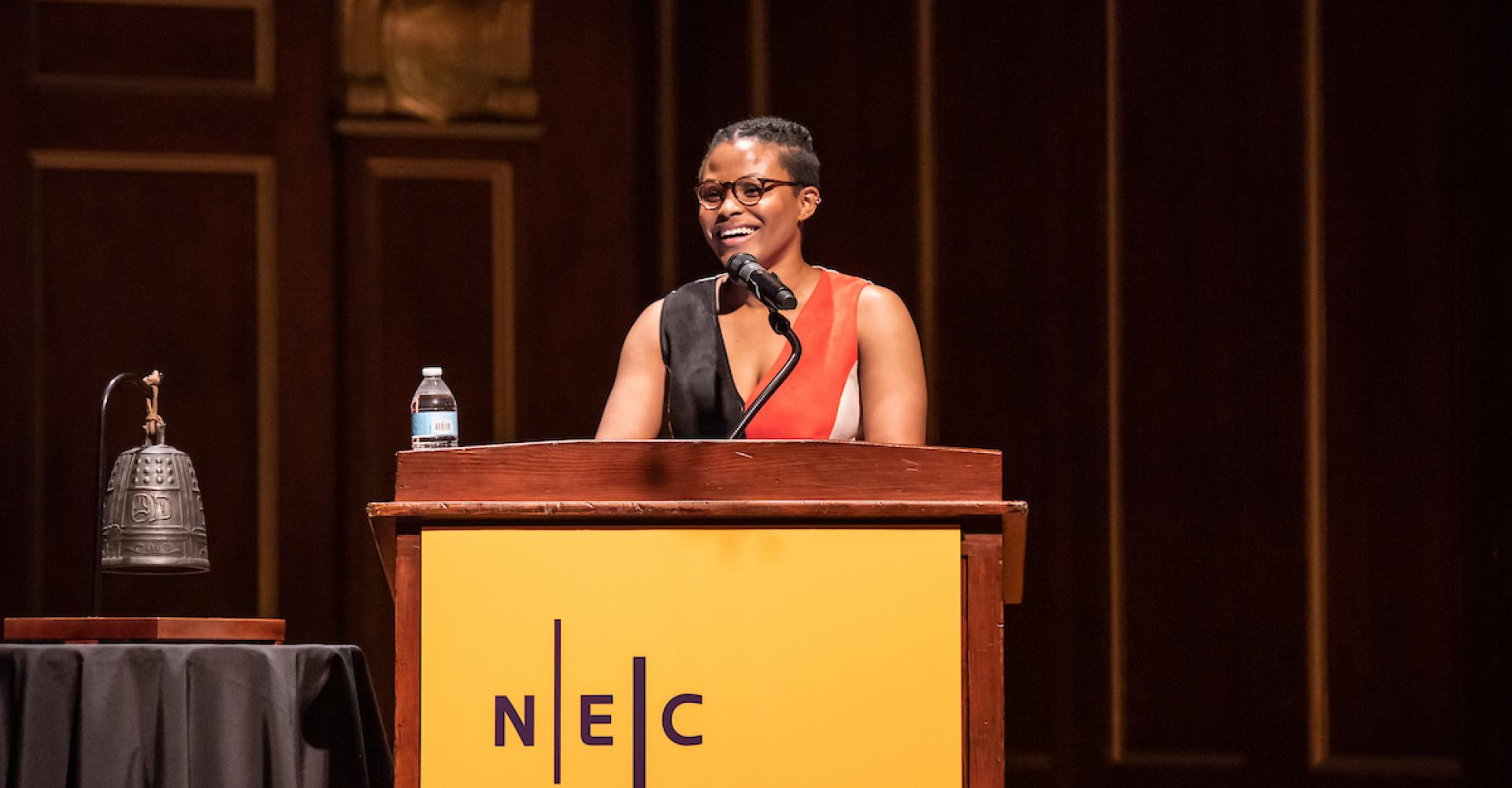 Robyn Smith delivers remarks at an NEC podium in Jordan Hall.