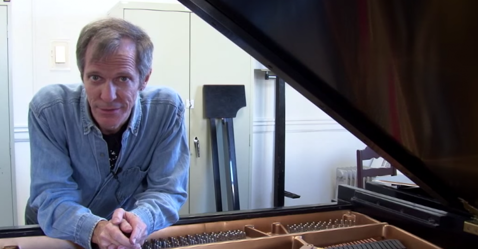 Steve Drury leans on a prepared grand piano looking at the camera