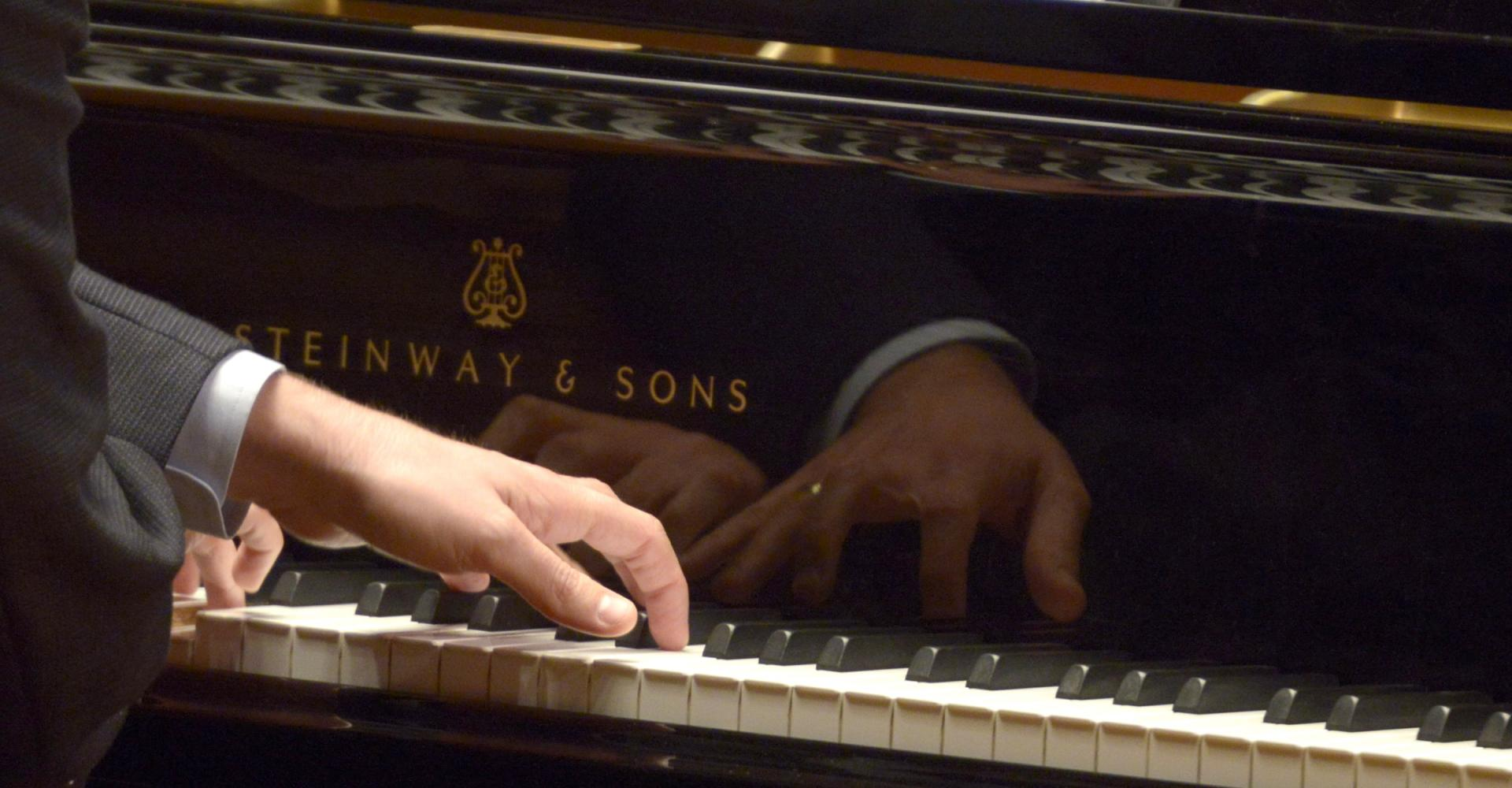 A piano player's hands playing piano.