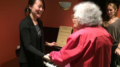 Pianist shakes hands with a senior citizen