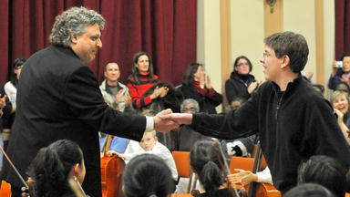 Steven Karidoyanes shakes hands with a young composer