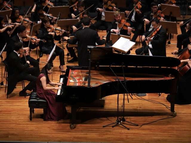 Xu Guo Performing on the Piano on stage at a competition