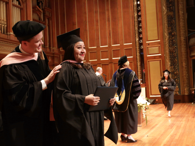 Julimar Alarcon smiles on the Jordan Hall stage as she receives her master's hood at commencement