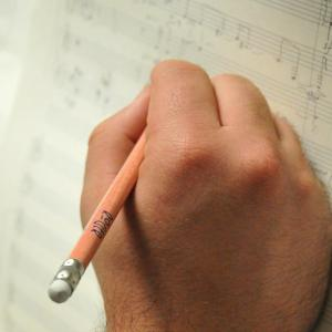 A composer writes on music page