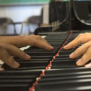 A closeup of a pianist's hands playing, with a close view of the piano keys.
