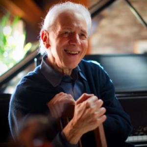 Pianist Russell Sherman smiles while seated at piano
