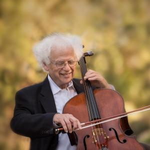 Laurence Lesser playing the cello and smiling, with green trees and plants in the background.