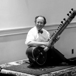 Peter Row holding a sitar