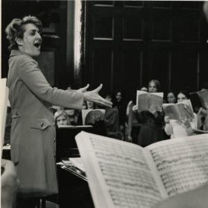 Lorna Cooke deVaron conducts while smiling and making a gesture of passion and joy.
