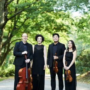 The Verona Quartet stands with their instruments under green-leafed trees.