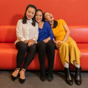 Three members of the Asian Student Association Executive Board smile and laugh while sitting on a couch.
