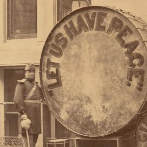 "Black and white photo of a man in a band uniform standing near a large drum. The drum says ""LET US HAVE PEACE."""