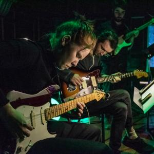 Two guitarists play with eyes closed, with dark green lighting, on Jordan Hall stage.