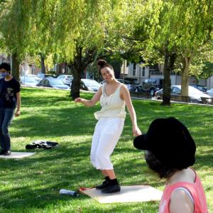 Jenny Herzog smiles while teaching tap in the park. Students are watching her. In the background is bright green grass and trees.