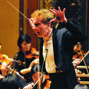 Hugh Wolff makes a dramatic gesture while conducting the Philharmonia orchestra on Jordan Hall stage.